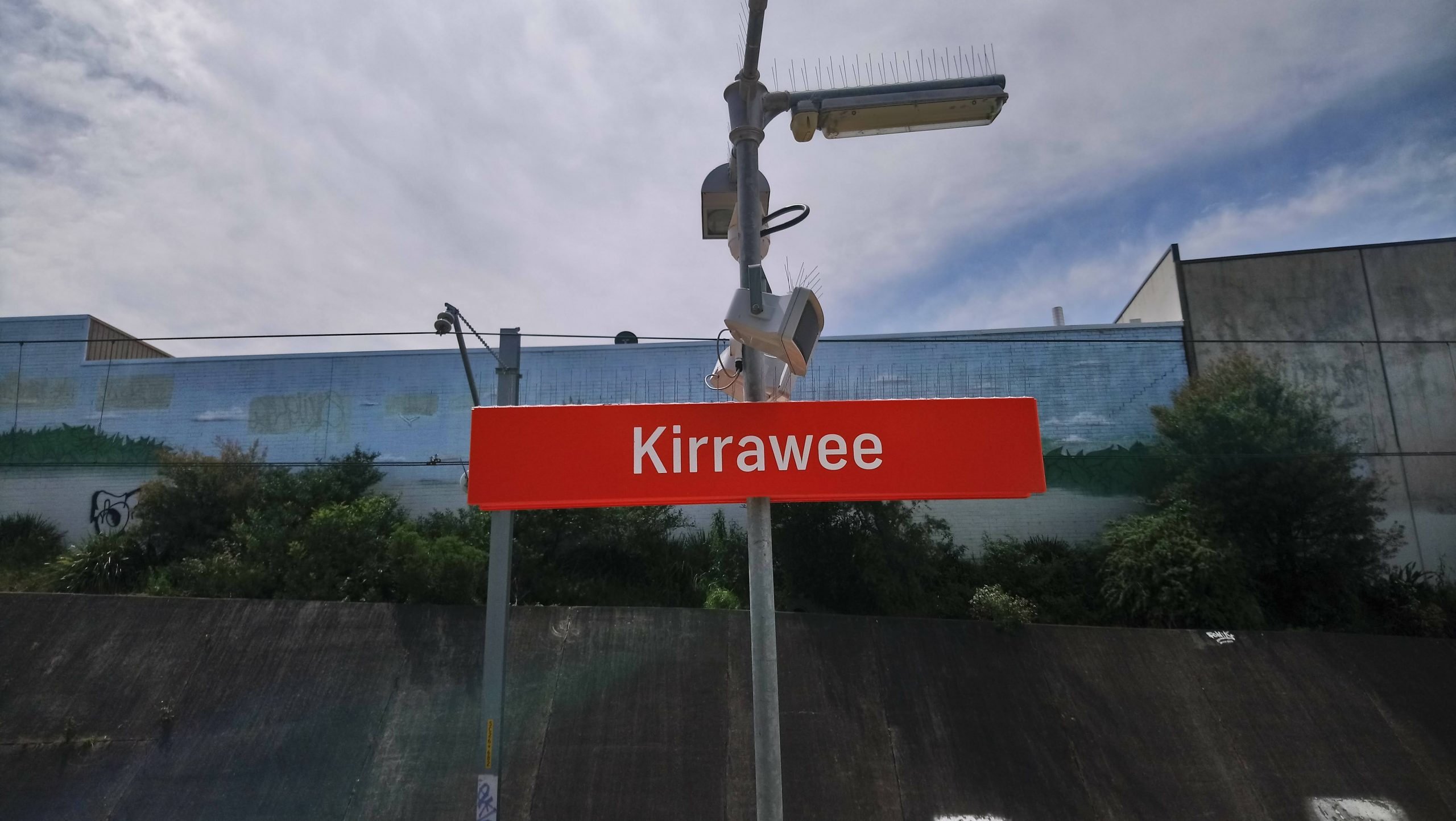An orange sign set in the middle of the photo marking the location of Kirrawee station. Background contains the back of factories with no windows.