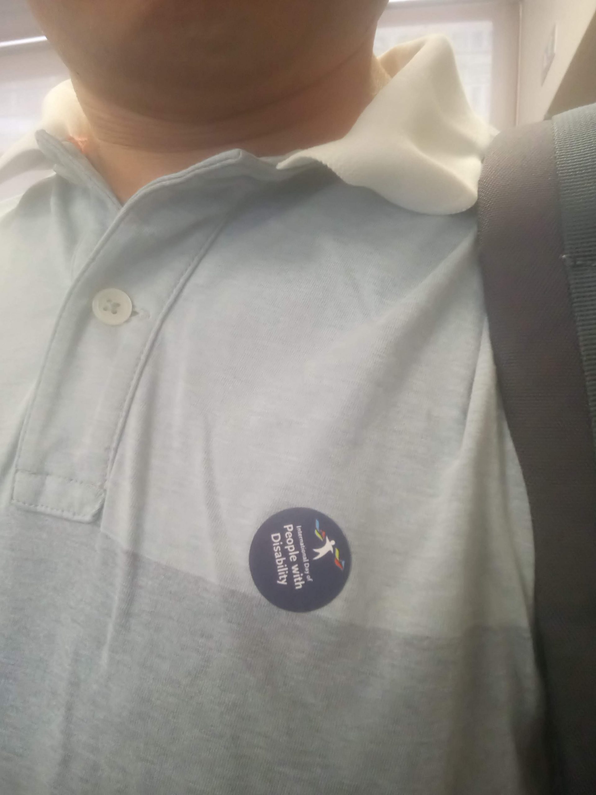 """A sticker on a shirt labelled """"International Day of People with Disability"""""""